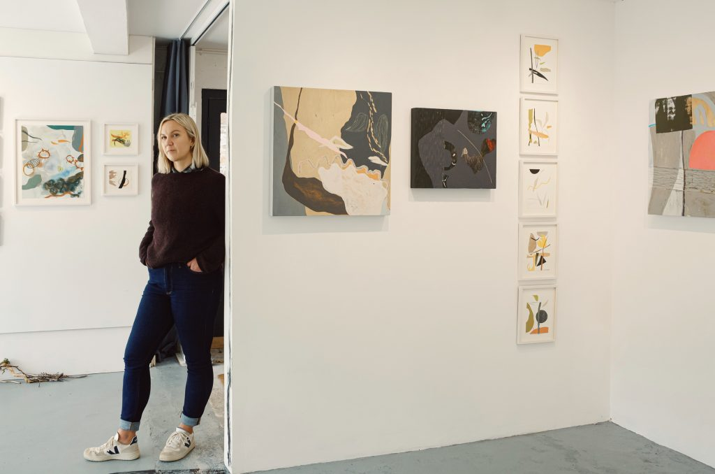 Artist Kitty Hillier standing in the gallery at Grays Wharf with her abstract paintings