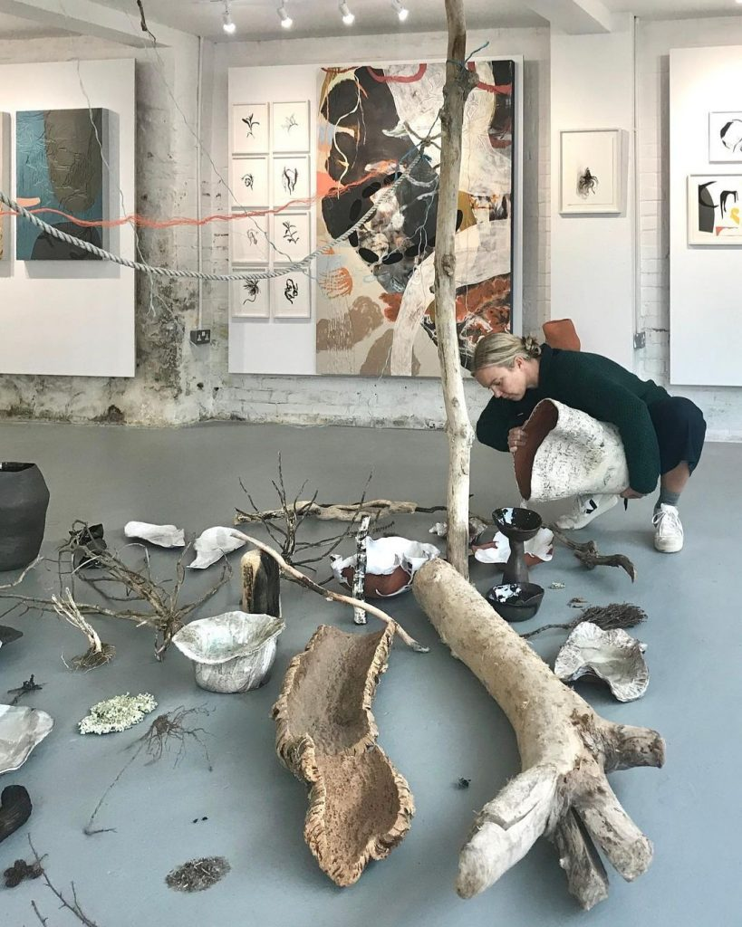 Kitty Hillier pouring collected rain water into vessels as part of installation 2020